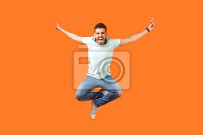 Naklejka Full length of crazy overjoyed brunette man in white outfit jumping in air with raised hands, screaming loud for joy, feeling energetic and lively. indoor studio shot isolated on orange background