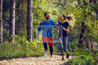 Naklejka Full length of fit sporty happy caucasian couple in sportswear running in woods on trail in morning.