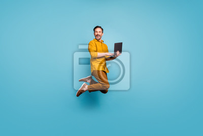 Naklejka Full size photo of funky man feel rejoice emotions jump use laptop search social media online black friday discounts wear casual style clothing isolated over blue color background