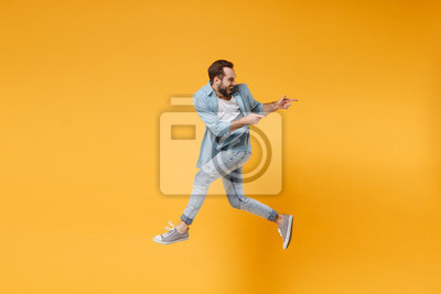 Naklejka Funny young bearded man in casual blue shirt posing isolated on yellow orange background, studio portrait. People emotions lifestyle concept. Mock up copy space. Jumping pointing index fingers aside.