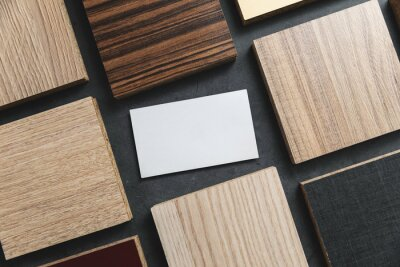 furniture material samples with blank business card on black stone background