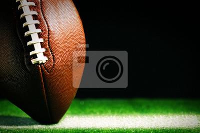 Naklejka Futbol amerykański na zielonej trawie, na czarnym tle
