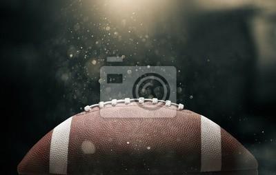 Naklejka Futbol amerykański piłka na czarnym tle oświetlony przez