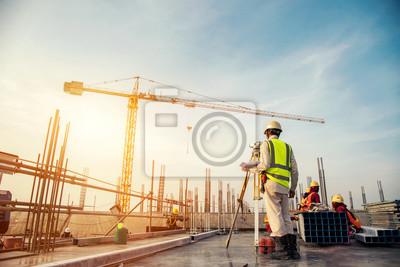 Naklejka Geodeta budowniczy Inżynier z Teodolitem tranzytowym wyposażeniem przy budową outdoors podczas ankiety pracuje