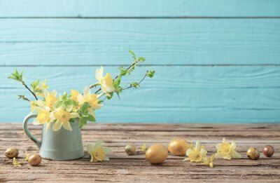 Naklejka Golden Easter eggs and yellow flowers on wooden background