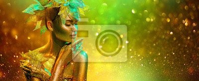 Golden Fashion model woman with bright golden sparkles on skin posing, fantasy flower, portrait of beautiful girl glowing makeup. Art design gold sequins make up. Glitter glowing skin, jewellery, neon