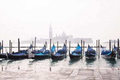 Gondolas on Grand Canal in Venice in foggy morning. Gondola service for tourist travel around Venice in Italy. Springtime. Copy space