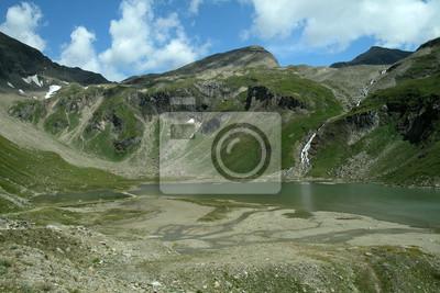 Góry w Austrii. Zielona trawa, skały i wody