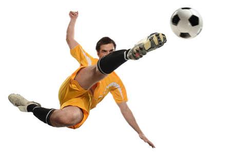 Gracz piłki nożnej kopania piłka podczas gdy skaczący odosobnionego nadmiernego białego tło