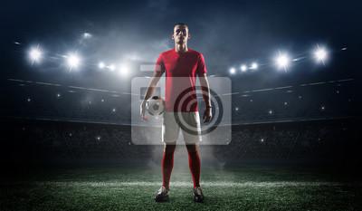 Naklejka Gracz piłki nożnej w stadium tle.