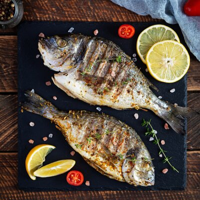 Naklejka Grilled dorado fish on wooden background. Roasted seafish with spice and herbs