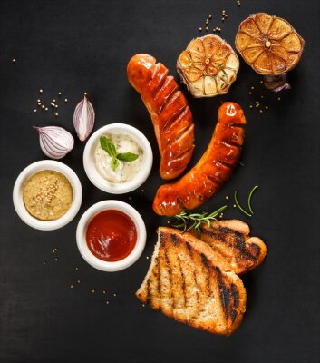 Naklejka Grilled sausages with different types of dips