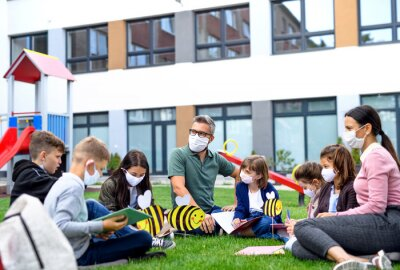 Group of cheerful children learning outdoors at school after covid-19 quarantine and lockdown.