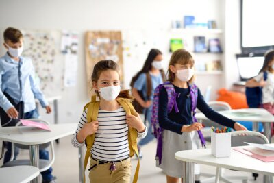 Naklejka Group of children with face mask back at school after covid-19 quarantine and lockdown.