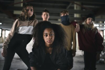 Naklejka Group of teenagers gang standing indoors in abandoned building, bullying concept.