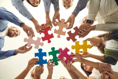 Naklejka Group of young and mature people making circle of colorful jigsaw puzzle parts, low angle shot from below. Happy business team enjoying teamwork, finding professional solution, starting new enterprise