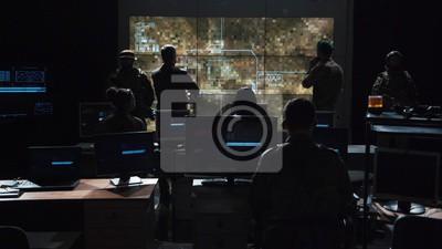 Naklejka Grupa żołnierzy lub szpiegów w ciemnym pokoju z dużymi monitorami i zaawansowaną technologią łączności satelitarnej, wystrzeliwującą pocisk. Obejmuje migające żółte światło.