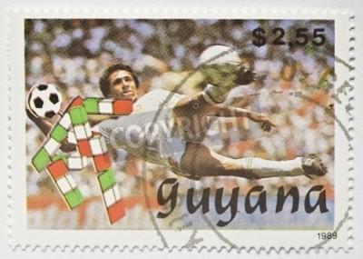 GUYANA - OKOŁO 1989 znaczek z Gujany pokazuje obraz piłkarz woleja piłkę, circa 1989
