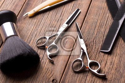 Naklejka Hairdressing tool kit. Scissors and other tool barber. Barber set. Barber tool on a wooden table. Scissors, comb for hair and a razor close-up.