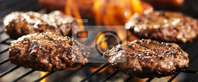 Naklejka hamuburgers cooking on grill outdoors in panoramic composition