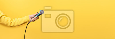 Naklejka hand holding microphone over yellow background, panoramic mock up image