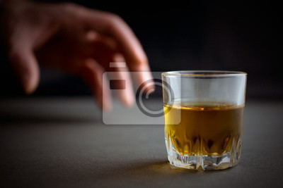 Naklejka hand reaches for a glass of whiskey or cognac or alcohol drink, alcoholism and alcohol abuse concept, defocused, selective focus, close up, gray table, dark background