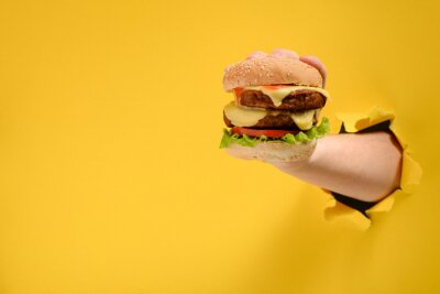 Naklejka Hand taking a big burger