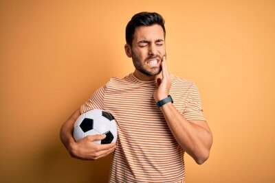 Handsome player man with beard playing soccer holding footballl ball over yellow background touching mouth with hand with painful expression because of toothache or dental illness on teeth. Dentist.