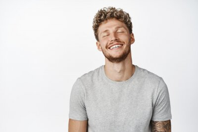 Naklejka Handsome smiling blond man close eyes, daydreaming, imaging something, having happy memory, standing in gray t-shirt over white background