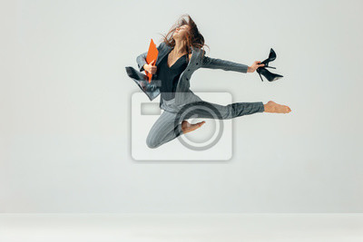 Naklejka Happy business woman dancing and smiling in motion isolated over white studio background. Human emotions concept. The businesswoman, office, success, professional, , happiness, expression concepts