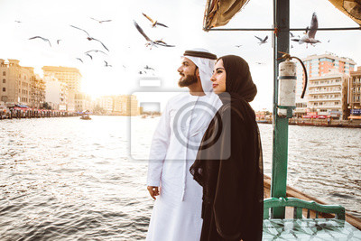 Naklejka Happy couple spending time in Dubai. man and woman wearing traditional clothes taking a cruise on the river