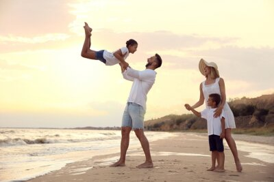 Happy family having fun on sandy beach near sea at sunset