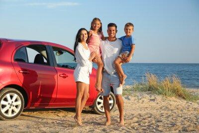 Happy family near car on sandy beach. Summer trip