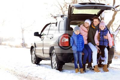 Happy family near car on winter day