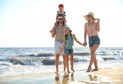 Happy family on sandy beach near sea