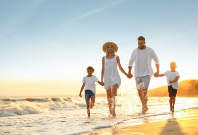 Naklejka Happy family on sandy beach near sea at sunset