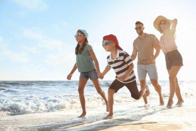 Happy family running on sandy beach near sea