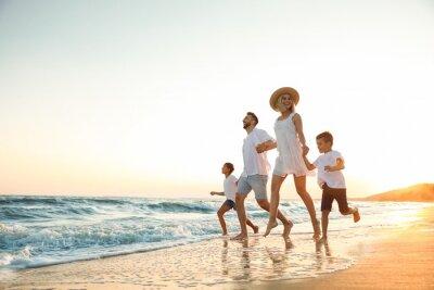 Happy family running on sandy beach near sea at sunset