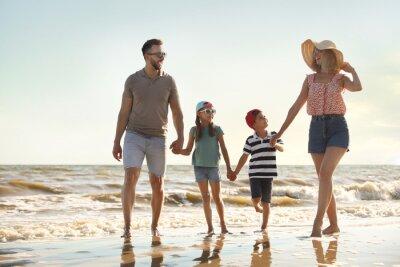 Happy family walking on sandy beach near sea