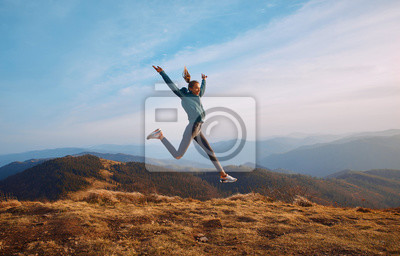 Naklejka Happy woman hiker jumping on mountain ridge on blue cloudy sky and mountains background. Travel and active lifestyle concept.