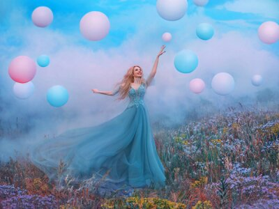 happy young beautiful blonde woman raised hand. Fantasy princess jumping touches pink ball air balloon. long blue tulle dress fluttering fly in wind. white clouds, fog, smoke colorful flowers meadow
