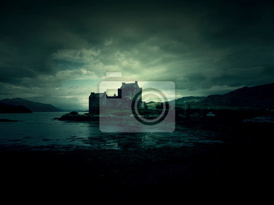 Naklejka haunted mystic eerie Eilean Donan Castle in Scotland with the sea around it and dark clouds