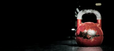 Naklejka Heavy old used color kettlebell weight on the gym floor ready for fitness strength workout to build muscles with dark background and free copy space banner