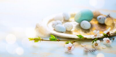 Holiday Easter banner or greeting card background; Spring tree flowers and Easter eggs on sunny light  wooden background