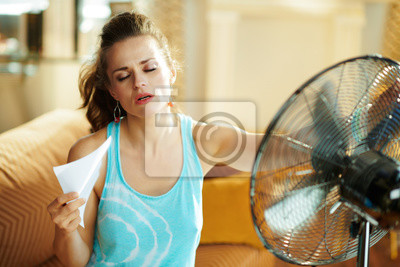 Naklejka hot woman in front of working fan suffering from summer heat