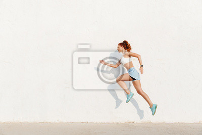 Naklejka Image of redhead young woman running along white wall while doing workout in morning