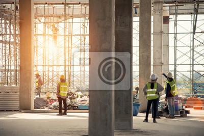 Naklejka Inżynierowie budowlani nadzorujący postęp projektu budowlanego stoją na nowym, betonowym dachu i dachu