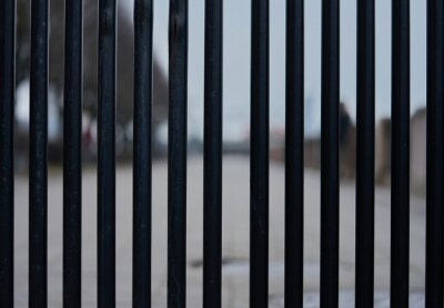 Iron wire fence closeup . Fence lattice texture background. Cloudy Sky