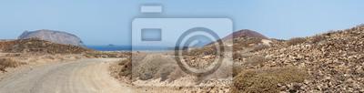 Naklejka Isole Canarie: la strada sterta na plaży Playa de Las Conchas i wulkan Montana Bermeja na La Graciosa, l'isola principale dell'arcipelago Chinijo a nord ovest di Lanzarote