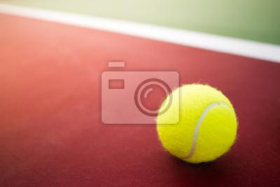 Jedna kula tenisowa na zielonym i czerwonym twardym dziedzińcu
